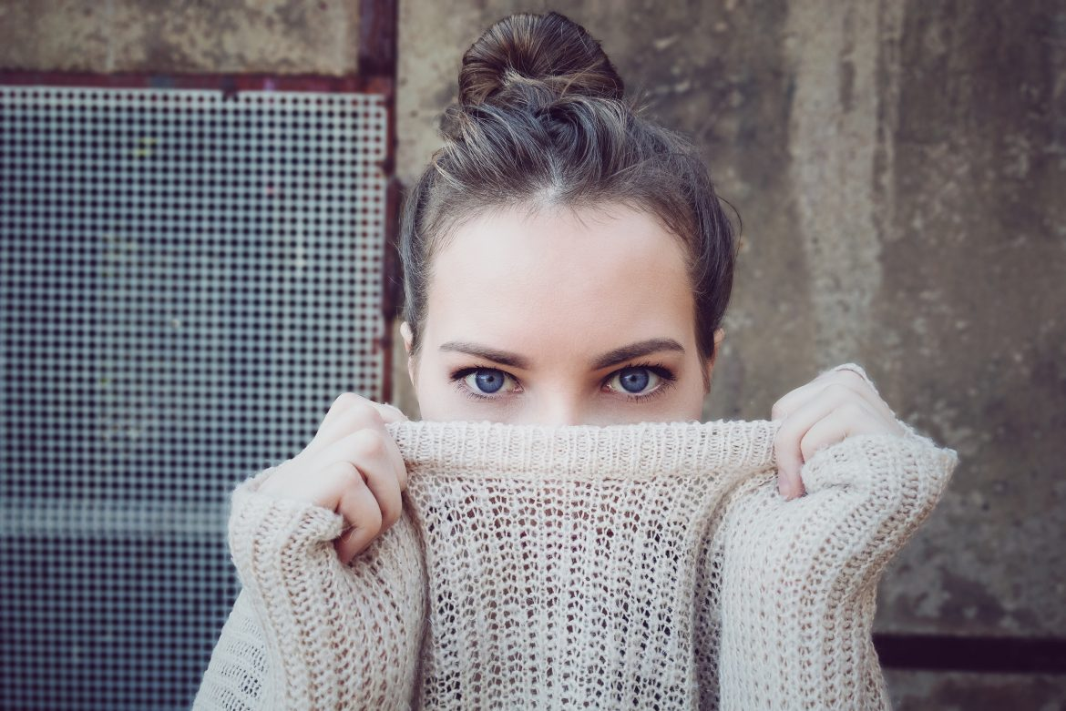 Photo of a girl holding her sweater over her month on Things You Shouldn't Say to thos Struggling with Infertility Blog on Not So Mommy...