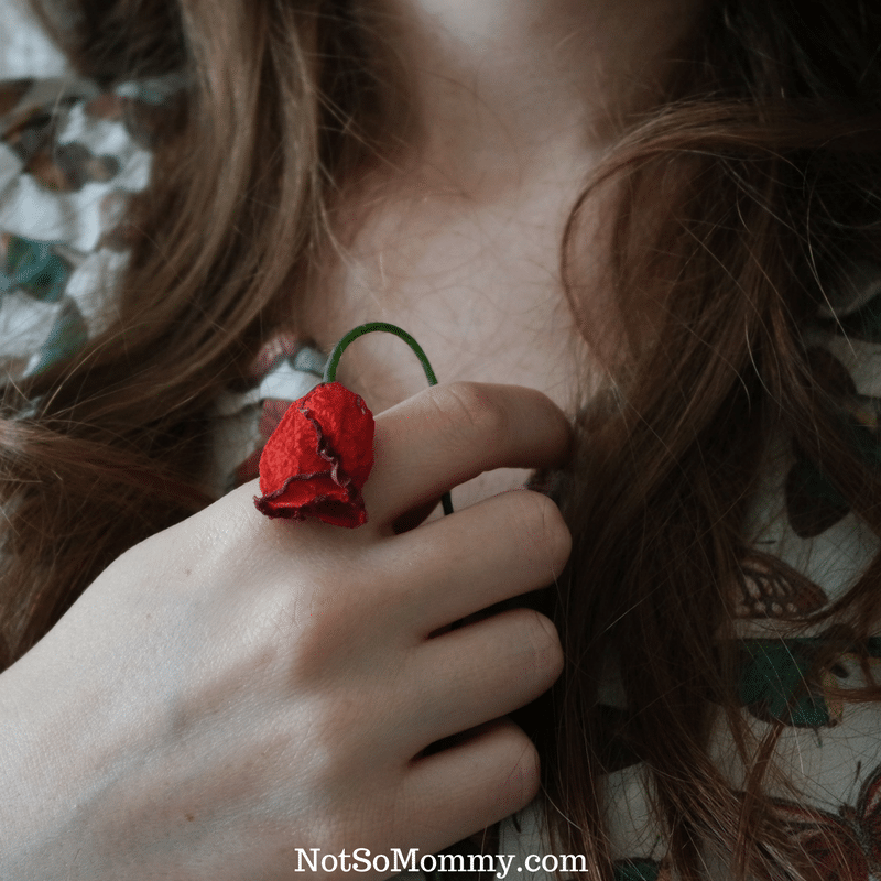 Photo of a woman holding a small, wilted red rose on Childless by... We all need more support, less judgment. Infertility Blog on Not So Mommy...