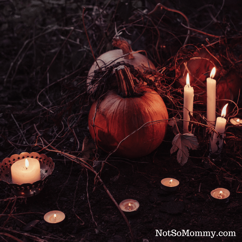 Photo of pumpkins with lit candles surrounding them on Day of the Dead: A Celebration of Life Infertility Blog on Not So Mommy...