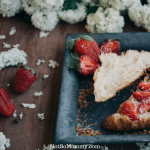 Photo of a croissant and strawberries on a blue plate with white flowers scattered around on table on Good Things: Comfort Foods Good Things Blog on Not So Mommy...