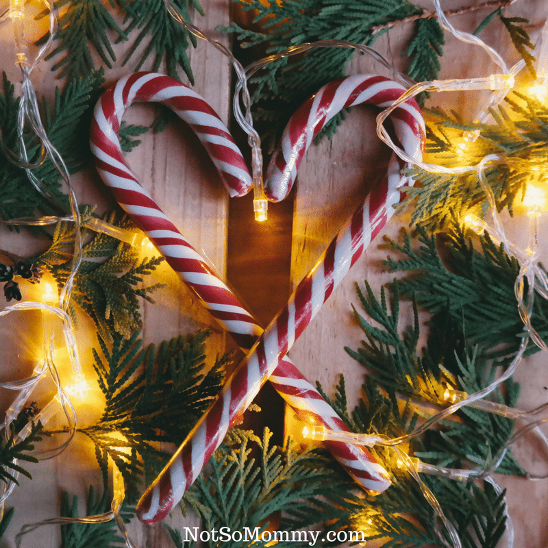 Photo of two candy canes forming a heart on top of Christmas greenery and lights on 17 Bright Sides of a Childless Christmas on Good Things Blog on Not So Mommy...