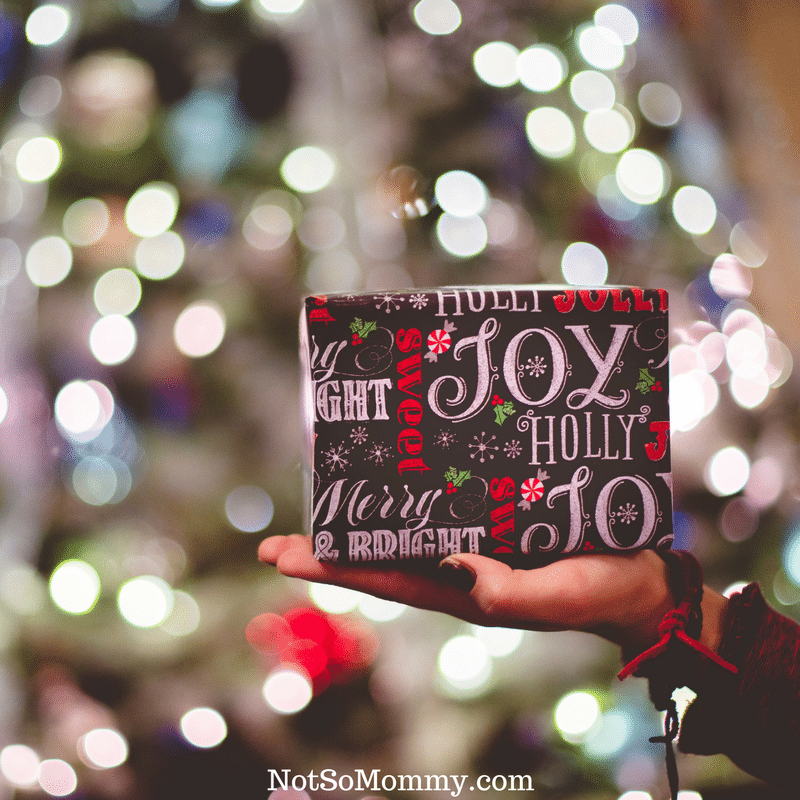 Photo of a hand giving a present wrapped in paper that says Joy on Spread Joy on Infertility Blog on Not So Mommy...