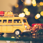 Photo of a yellow van with luggage on top set in front of a Christmas Tree with twinkling lights on The Season of Family: A Childless Woman's Perspective on Infertility Blog on Not So Mommy...