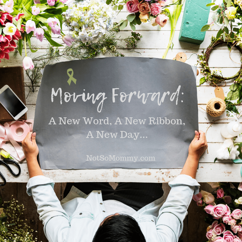 Photo of a woman holding a piece of black construction paper and surrounded by flowers and other supplies on Moving Forward: A New Word, A New Ribbon, A New Day on Not So Mommy..., a childless blog