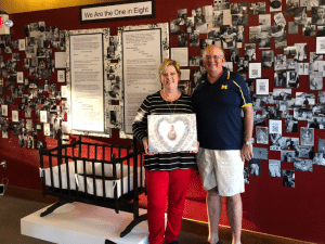 "Photo of Sue Johnston and her husband in front of her ArtPrize 2018 Exhibit, ""We Are the One in Eight"""