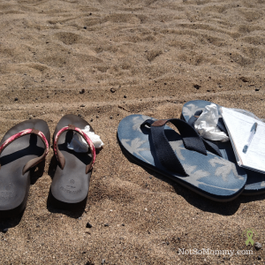 Photo of two pairs of flip-flops sitting on a beach with a line drawn in the sand on Claire's CNBC Story: A Line in the Sand on Not So Mommy..., a childless blog
