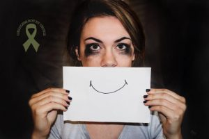 """Photo of a woman with tear-stained eyes, holding a piece of paper with a smile drawn on it that that covers her mouth on """"The Childless Not By Choice Awareness Ribbon: A Symbol of..."""" on Not So Mommy..., a childless blog"""
