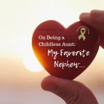 """Photo of a person holding a small red heart in between their thumb and first two fingers with sunlight in the background on """"On Being a Childless Aunt: My Favorite Nephew . . . """" on Not So Mommy..., a childless blog"""